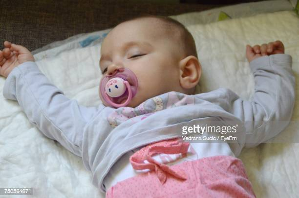 High Angle View Of Baby With Pacifier On Sheet At Home