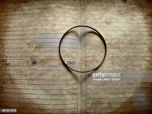 High Angle View Of Bangle Forming Heart Shape On Book