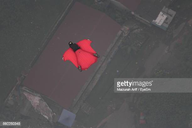 High Angle View Of Base Jumper Flying In Mid-Air