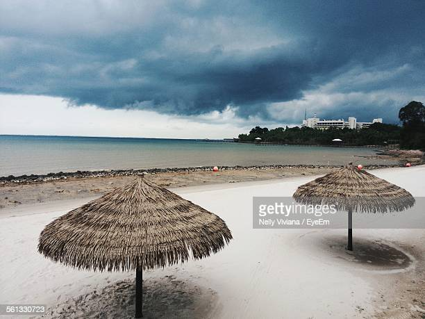 High Angle View Of Beach Umbrellas On Shore By Sea Against Cloudy Sky