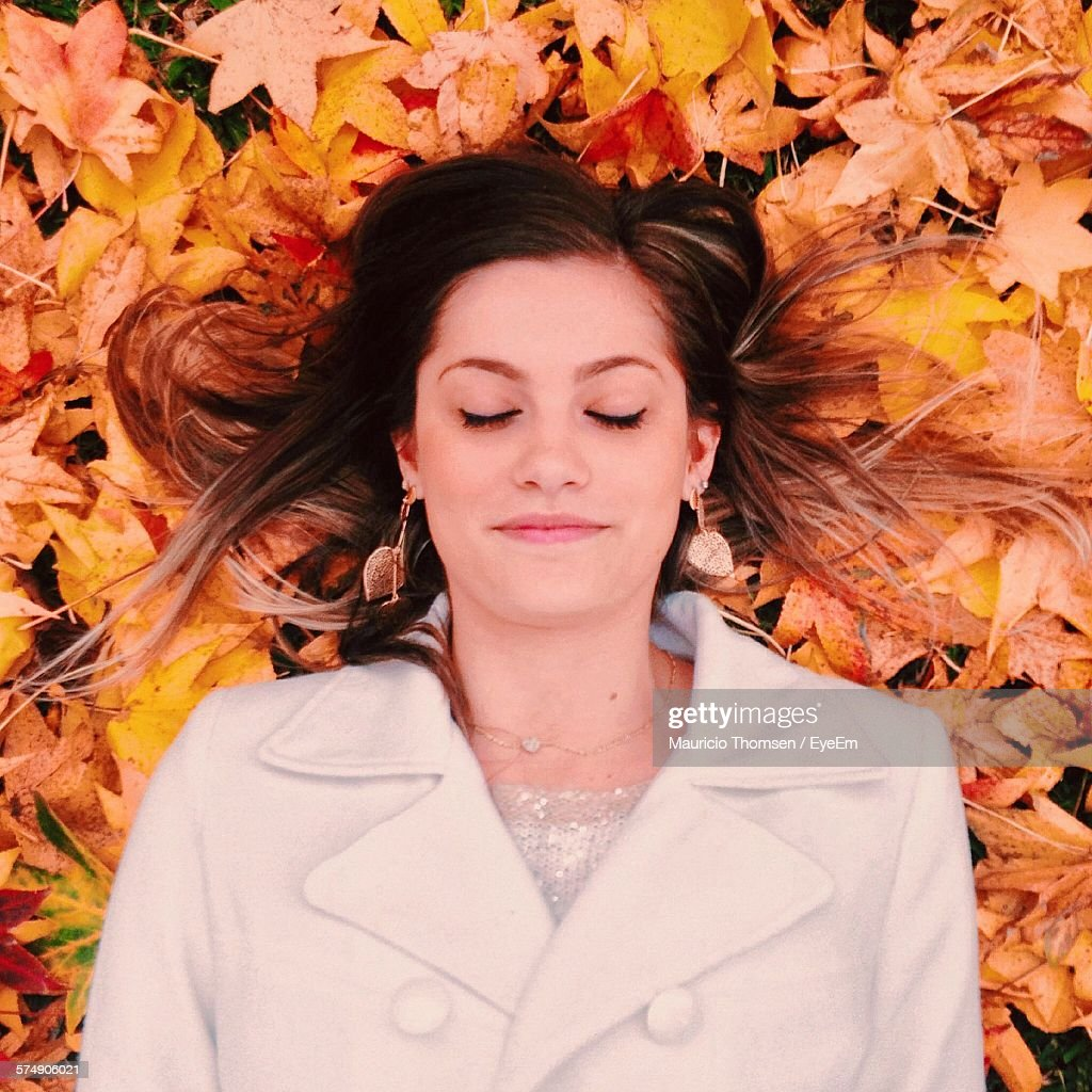 High Angle View Of Beautiful Young Woman Sleeping On Autumn Leaves