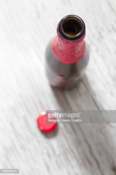 High Angle View Of Beer Bottle On Plank