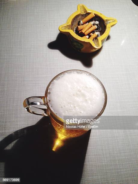 High Angle View Of Beer Glass And Cigarette Butts