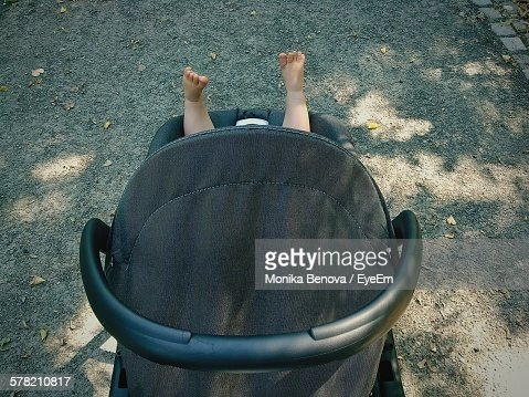 High Angle View Of Black Baby Carriage With Feet Up