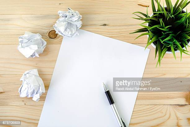 High Angle View Of Blank Sheet Of Paper On Wooden Floor