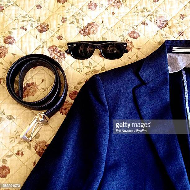 High Angle View Of Blazer With Belt And Sunglasses On Bed