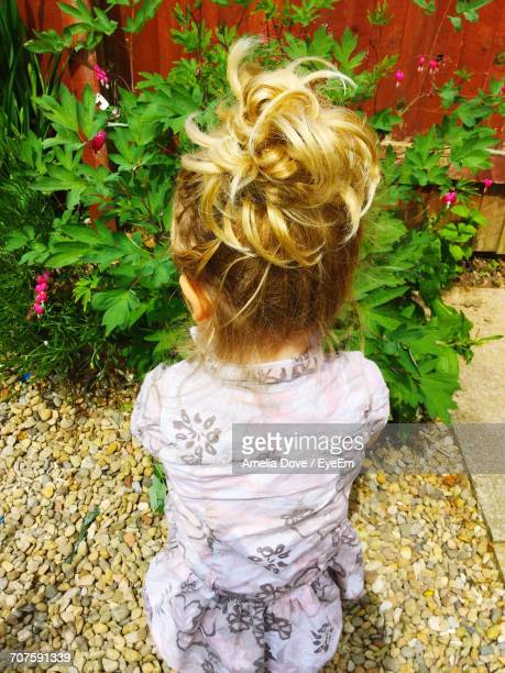 High Angle View Of Blond Girl Standing By Plants In Yard