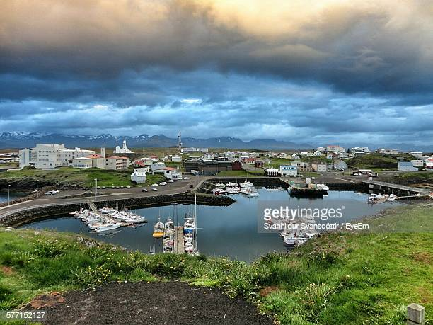 High Angle View Of Boats At Harbor Against Cloudy Sky At Stykkisholmur
