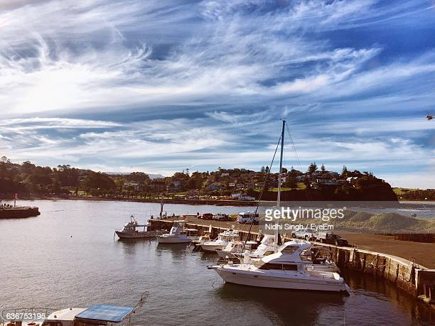 High Angle View Of Boats Moored At Harbor Against Cloudy Sky