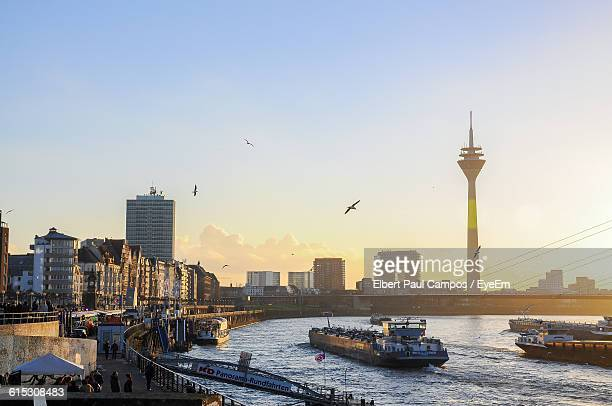 High Angle View Of Boats Sailing In Rhine River Against Rheinturm At Sunset