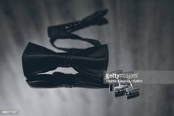 High Angle View Of Bow Tie And Cuff Link On Table