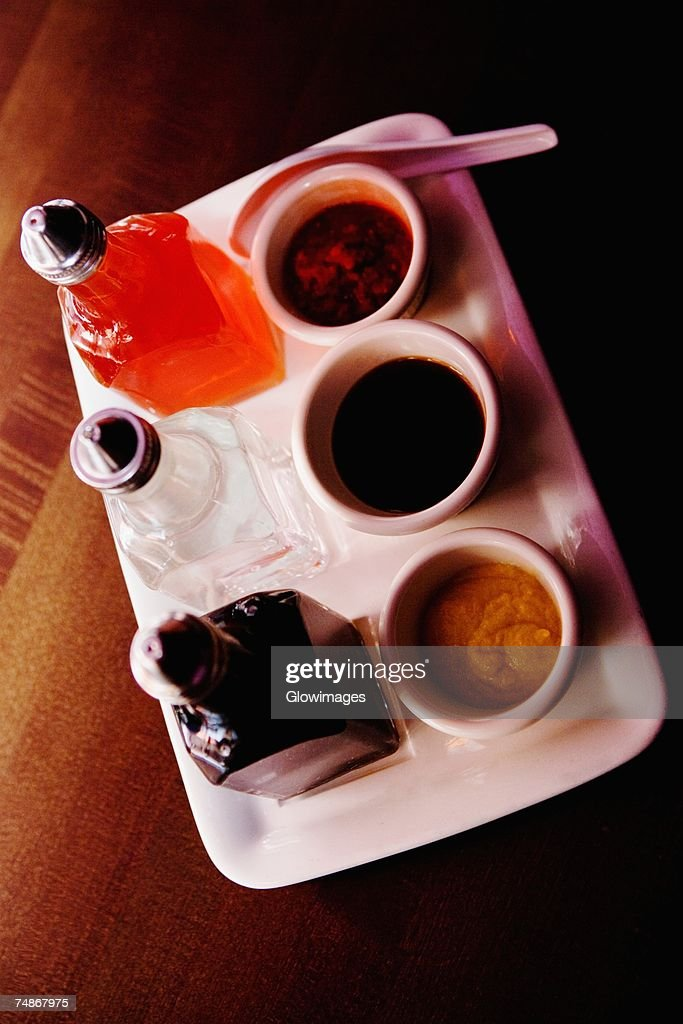 High angle view of bowls of soups with sauce bottles on a tray : Stock Photo