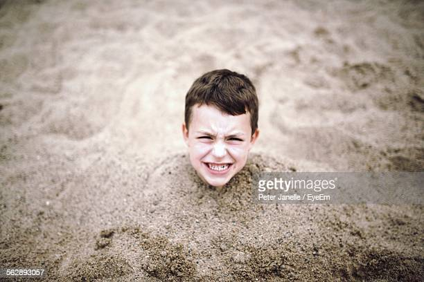 High Angle View Of Boy Buried In Sand