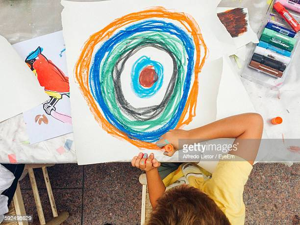 High Angle View Of Boy Drawing At Table