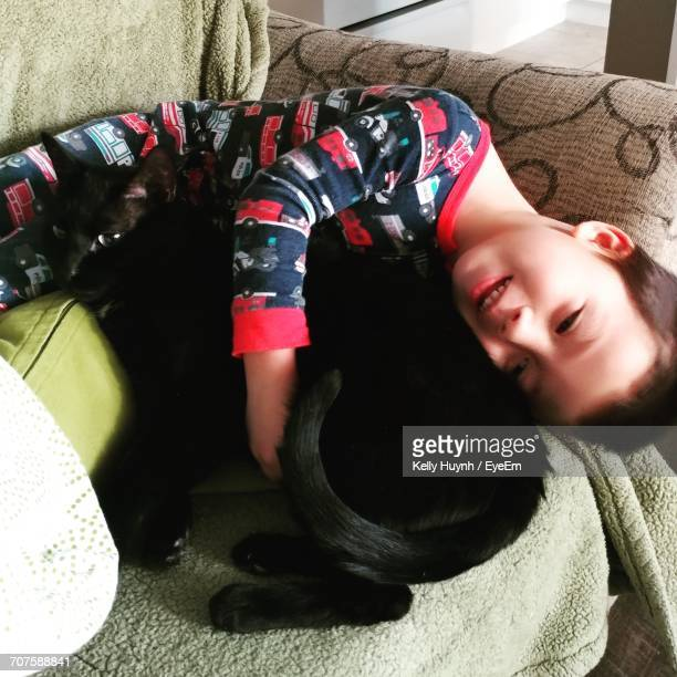 High Angle View Of Boy Embracing Cat While Lying On Sofa At Home