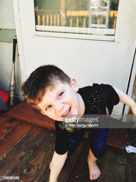 High Angle View Of Boy Making Face While Standing On Hardwood Floor