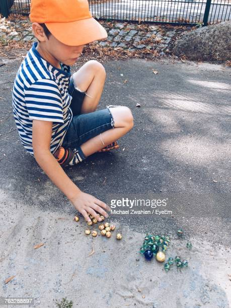 High Angle View Of Boy Playing Marbles On Footpath