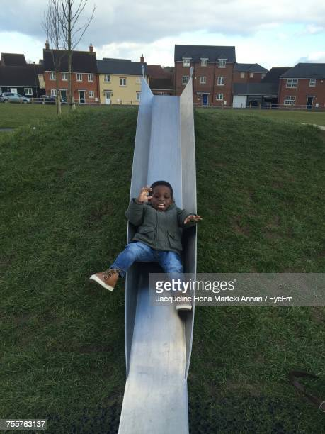 High Angle View Of Boy Playing On Slide At Hill Against Buildings