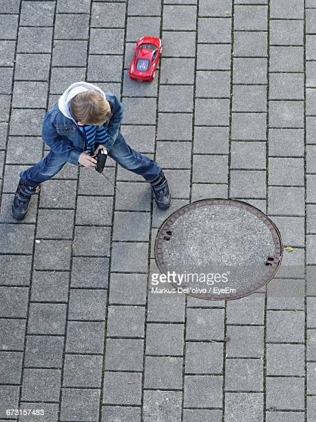 High Angle View Of Boy Playing With Remote Control Car On Footpath