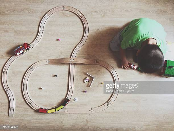 High Angle View Of Boy Playing With Toy Train At Home