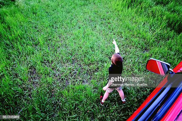 High Angle View Of Boy Pointing Finger On Grassy Field
