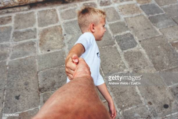 High Angle View Of Boy Pulling Hand Of Father Outdoors