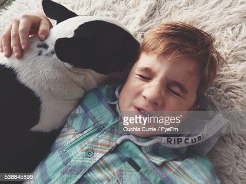 High Angle View Of Boy Relaxing With Dog On Bed At Home