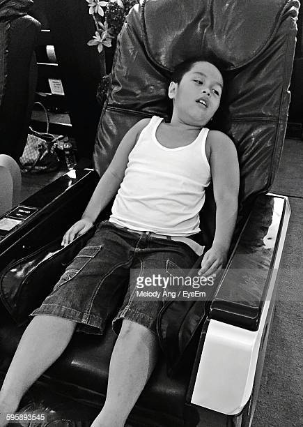 High Angle View Of Boy Resting On Massage Chair