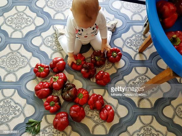 High Angle View Of Boy Sitting By Vegetables