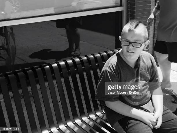High Angle View Of Boy Sitting On Bench
