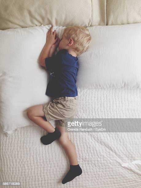 High Angle View Of Boy Sleeping On Bed