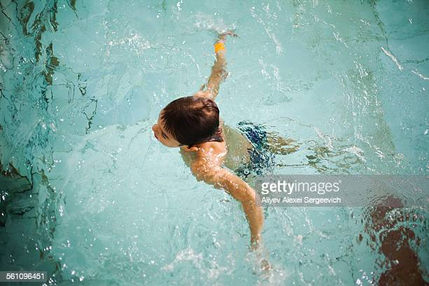 High angle view of boy treating water in swimming pool