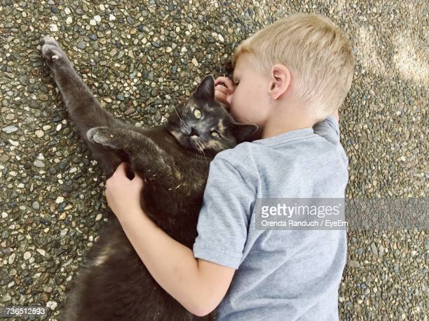 High Angle View Of Boy With Black Cat Lying On Street