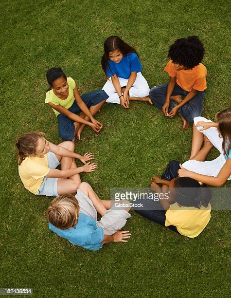 High angle view of boys and girls sitting on grass