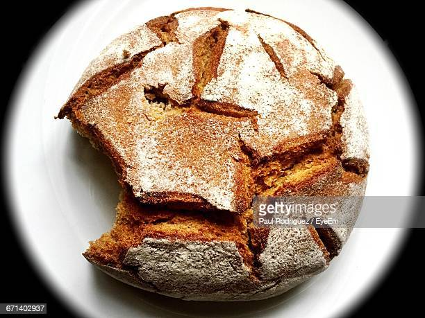 High Angle View Of Bread With Missing Bite In Plate