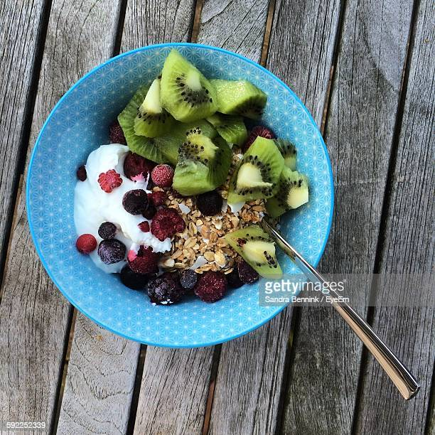 High Angle View Of Breakfast In Blue Bowl On Wooden Table