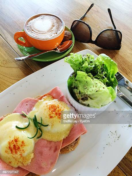 High Angle View Of Breakfast Served In Plate By Coffee Cup And Sunglasses On Wooden Table