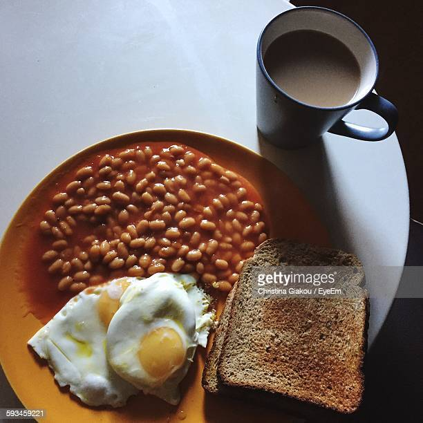 High Angle View Of Breakfast Served In Plate By Coffee Cup On Table