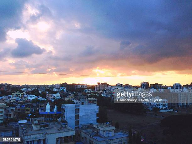 High Angle View Of Buildings Against Cloudy Sky At Sunset