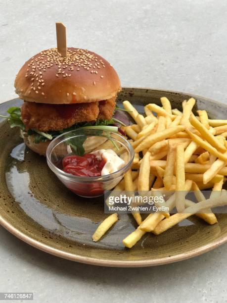 High Angle View Of Burger And French Fries Served In Plate On Table