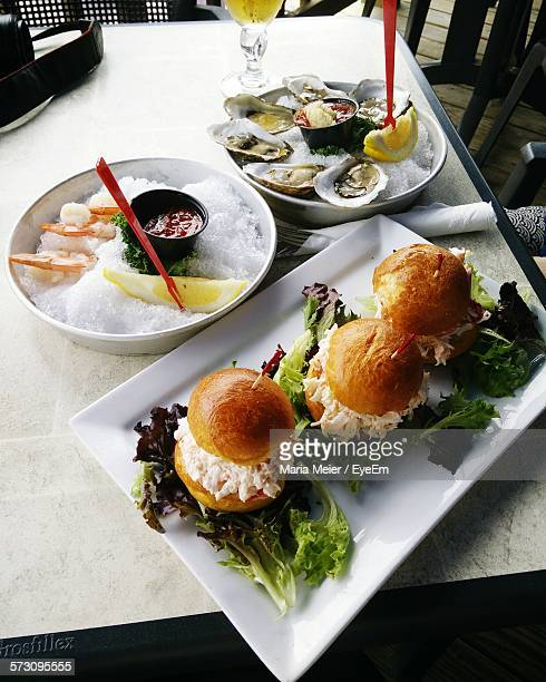 High Angle View Of Burger And Oysters Served On Table