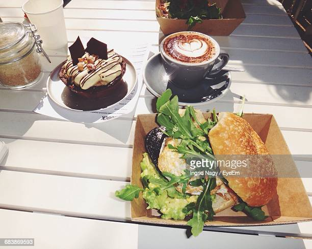 High Angle View Of Burger In Plate And Coffee Cup On Table