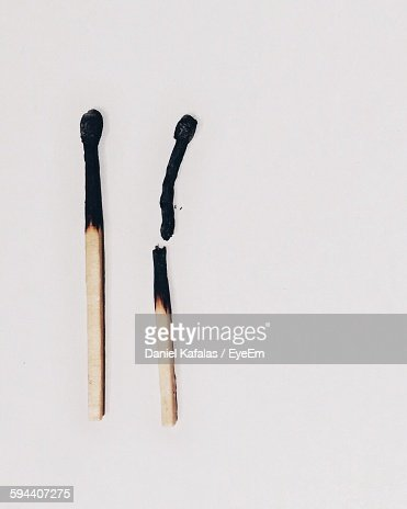 High Angle View Of Burnt Matchsticks Against White Background