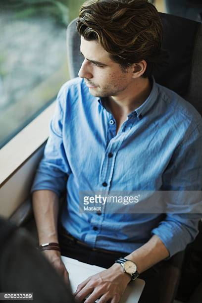 High angle view of businessman looking out through train window