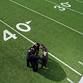 high angle view of businessmen in a huddle on a football field
