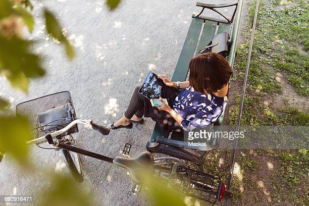 High angle view of businesswoman using digital tablet on park bench