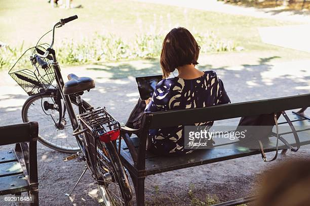 High angle view of businesswoman using digital tablet while sitting on park bench