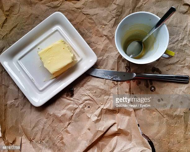 High Angle View Of Butter In Plate By Cup On Paper