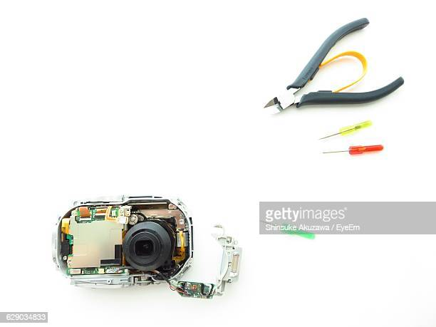 High Angle View Of Camera And Tools Over White Background