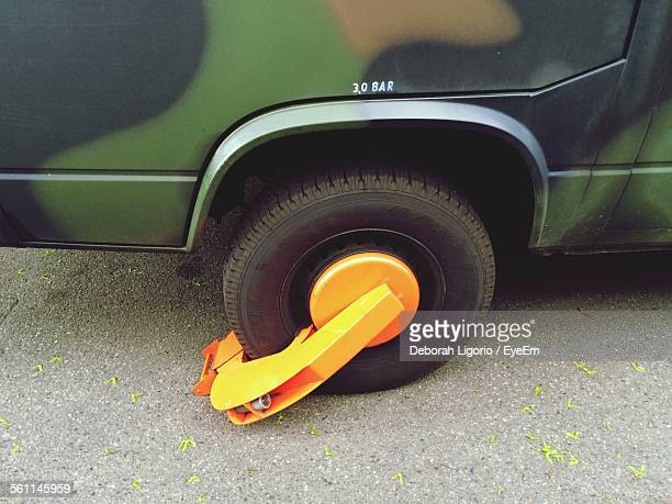 High Angle View Of Car Wheel Clamp Parked On Street